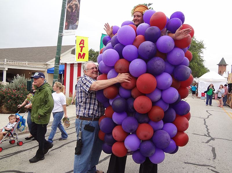Man hugging Grape Stilt Walker