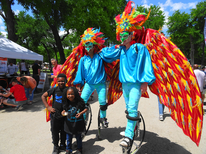 Bird stilt walkers with kids
